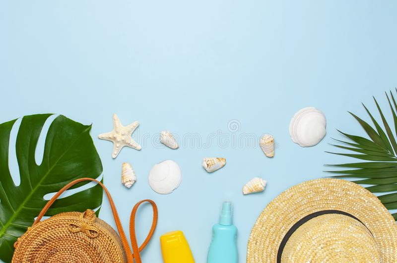 Summer composition flat lay. Round trendy rattan bag straw hat tropical palm leaves coconut sunscreen seashells on blue background royalty free stock photos