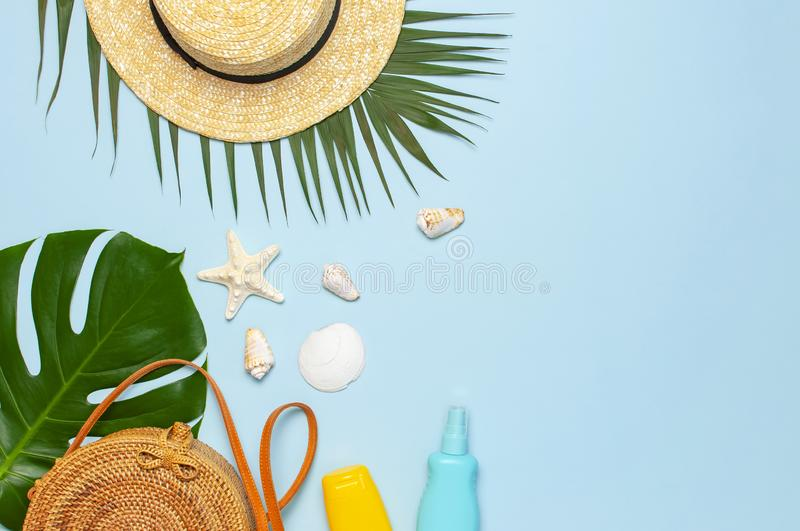Summer composition flat lay. Round trendy rattan bag straw hat tropical palm leaves coconut sunscreen seashells on blue background stock images