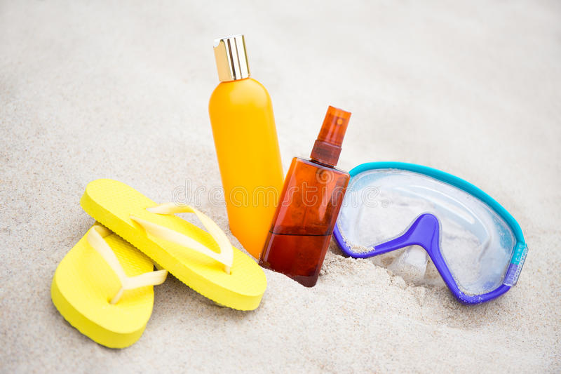 Summer concept - close up of flip flops, suntan lotion bottles a. Nd diving mask in sand on the beach stock photos
