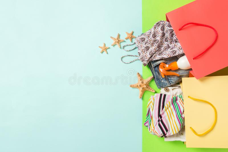 Summer concept of colourful shopping bags full of clothes. Gift bags with T-shirt, denim shorts, flip flops and bottle of royalty free stock image