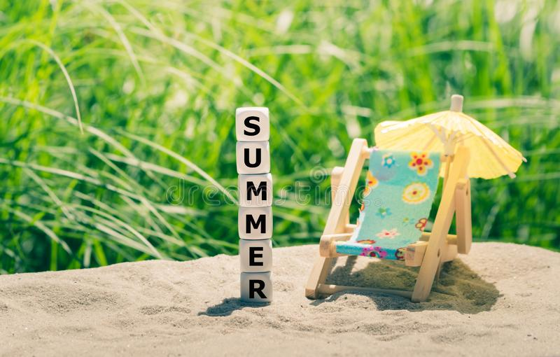 Summer concept. Dice placed on a beach form the word `summer`. Next to a beach chair stock images