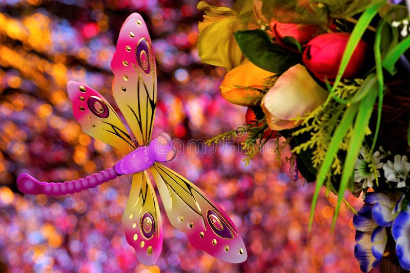 Summer concept, dragonfly flies on a bouquet of flowers, on a rainbow bokeh background. Flowers garden decoration pleasing to the stock image