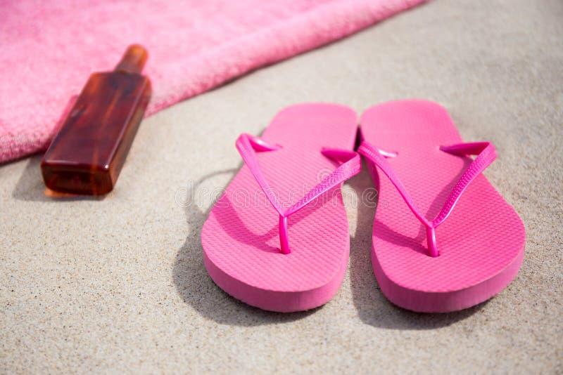 Summer concept - flip flops, towel and suntan lotion bottle on s. Summer concept - pink flip flops, towel and suntan lotion bottle on sandy beach royalty free stock photos