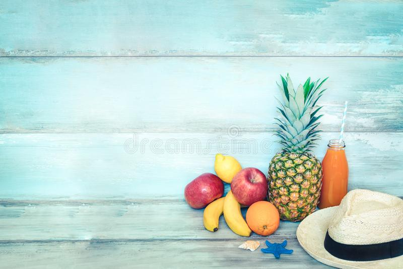 Summer concept stillife - a pile of fresh fruits, straw hat and a bottle of multivitamin juice in front of a blue rustic wooden. Background stock images