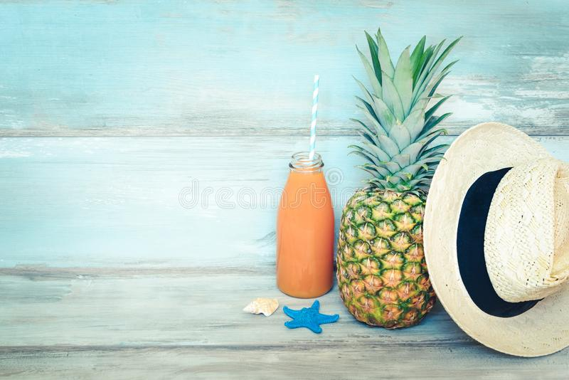 Summer concept stillife - ripe pineapple, straw hat and a bottle of multivitamin juice in front of a blue rustic wooden background.  stock photos