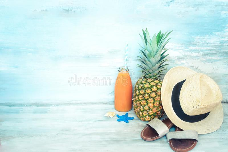 Summer concept stillife - ripe pineapple, straw hat, flip-flops and a bottle of multivitamin juice in front of a blue rustic. Wooden background stock photography
