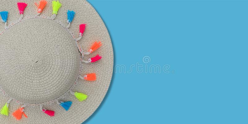 Summer concept template or mock up. Top view on straw beach hat with ribbon and multi colored pompons on blue background. Top view.  stock image