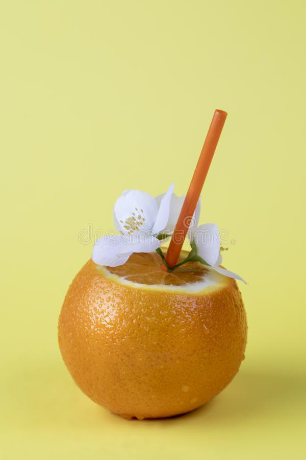 Summer concept vertical image of a fresh orange on a yellow background. Summer fresh orange juice and small white flower royalty free stock photos