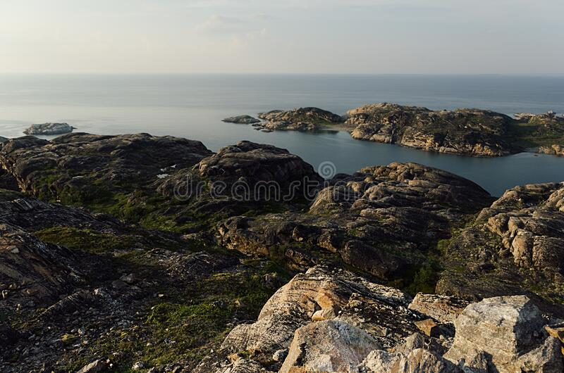 Summer contrast norway landscape, sunset - granite high shore and quiet Arctic Ocean in sunny weather. Summer contrast norway landscape, sunset - granite high stock photos