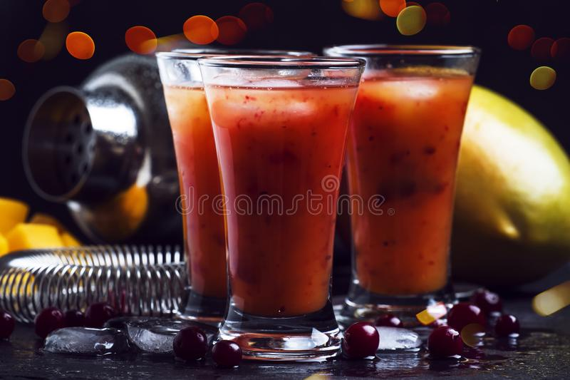 Summer cool alcoholic cocktail mango liqueur and cranberry on black bar counter background, selective focus royalty free stock image