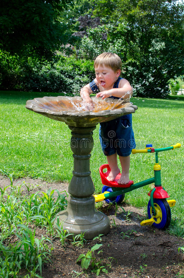 Summer cool off boy and bird bath. A cute little boy finds a unusual way to cool off on a hot summer's day... who said bird baths were just for the birds stock images