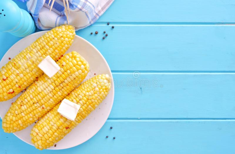 Summer corn on the cob, top view, side border on blue wood. Summer corn on the cob. Top view scene, side orientation on a blue wood background royalty free stock photos