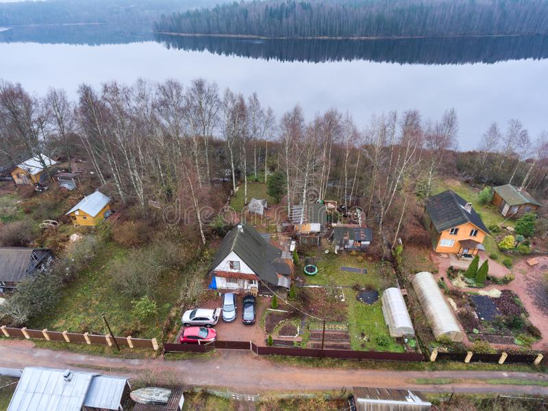 Summer cottage with courtyard, barns and small garden is on lake shore. Aerial view at spring season. Russia royalty free stock photography