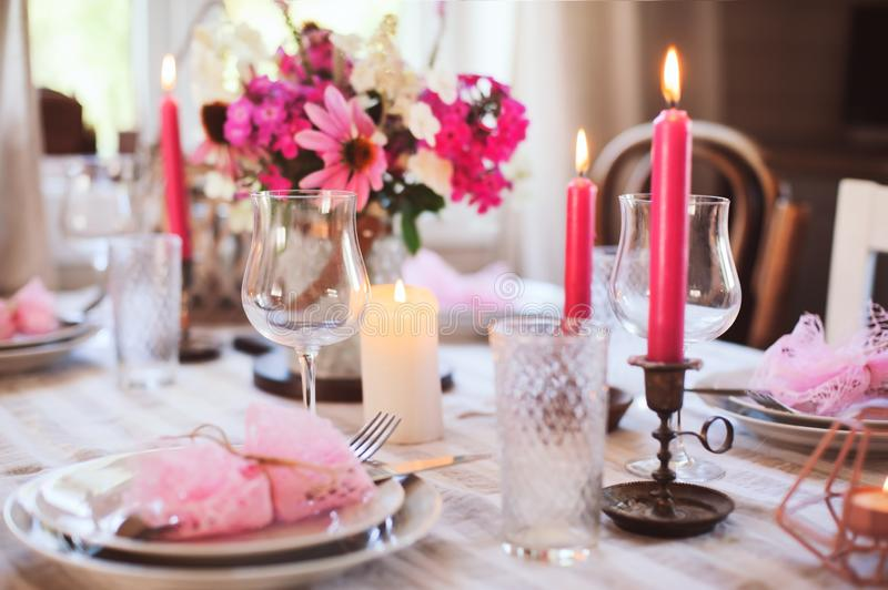 Summer cottage kitchen decorated for festive dinner. Romantic table setting with candles and flowers royalty free stock photo