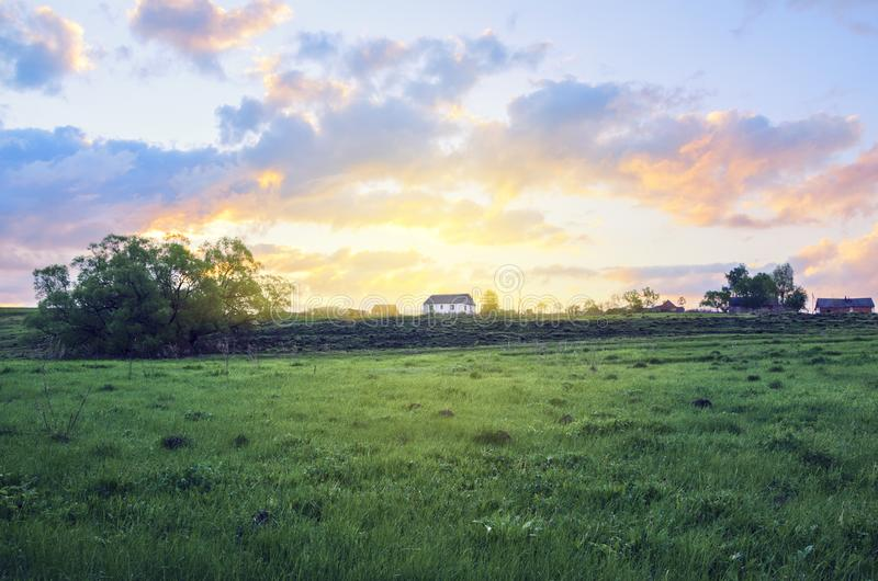 Empty green meadow on a background of country house and rising sun. Summer country landscape with beautiful clouds in sky at sunrise royalty free stock photography