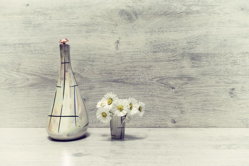 Summer creative still life in minimal style. White and pink Marguerite daisy flowers in vintage pearl flagon and in small liqueur royalty free stock photography