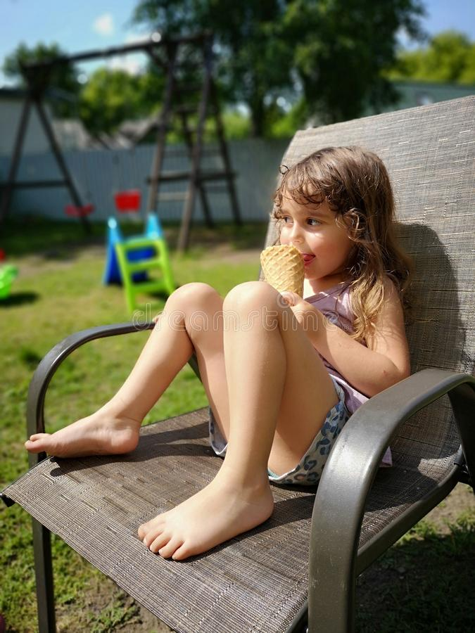 Summer. Cute girl with icecream sitting in armchair royalty free stock image