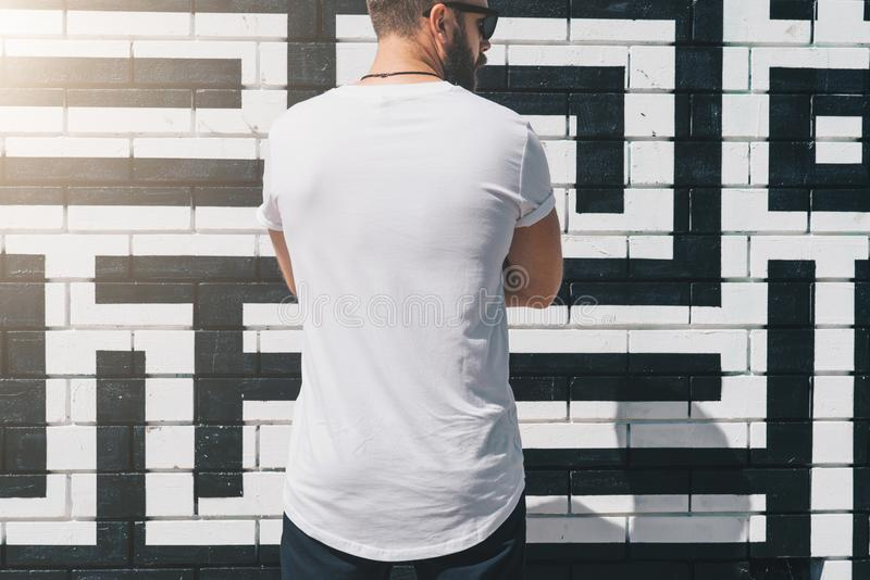Back view. Young bearded millennial man dressed in white t-shirt is stands against brick wall. Mock up. stock photos