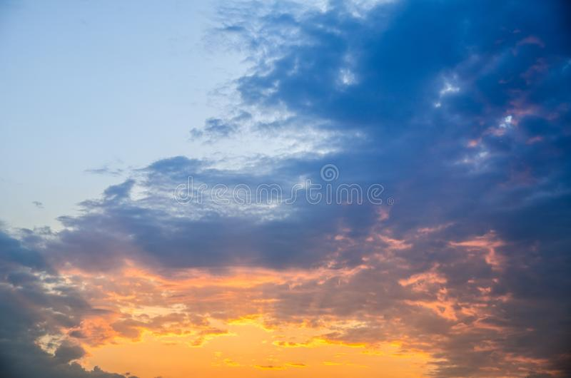 Summer day beautiful cloudy sunset backdrop, natural landscape photography with golden-blue colorful sky, sun rays from bottom royalty free stock image