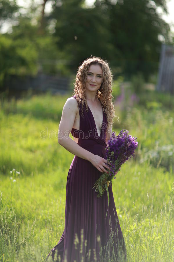 Summer day. Beautiful girl with flowers on a great summer day stock image