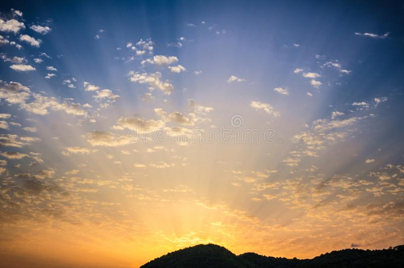 Summer day beautiful sunset with golden cloudy colorful sky and amazing radiant sun rays coming from behind the hills royalty free stock images