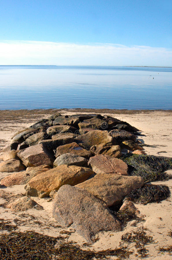 Summer day on the Cape. Calm, hot summer day on Cape Cod beach showing rock pile, seaweed, sand, blue sky, calm blue ocean, buoys. Seals frequent the area royalty free stock image