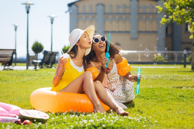 Delighted happy women sitting on the grass royalty free stock photo
