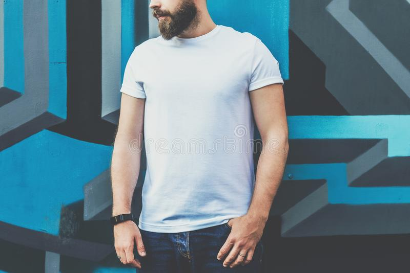 Front view. Young bearded hipster man dressed in white t-shirt is stands against wall with graffiti. Mock up. stock image