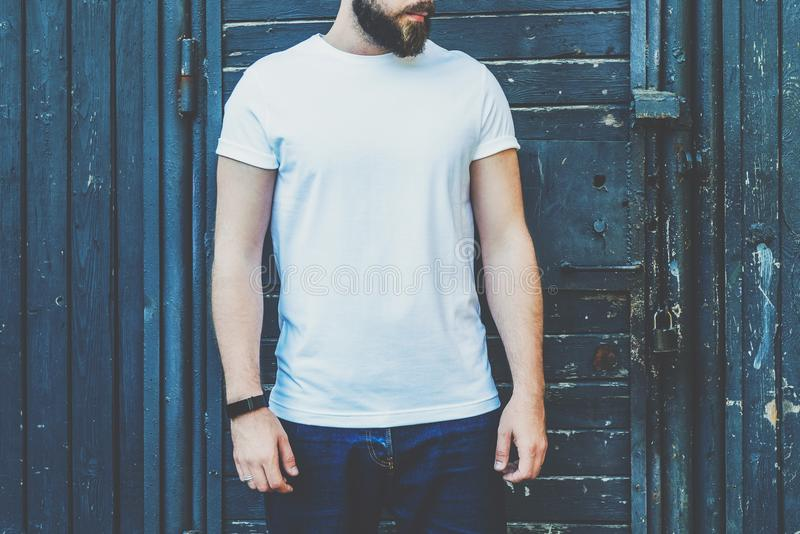 Front view. Young bearded hipster man dressed in white t-shirt and sunglasses is stands against dark wood wall. royalty free stock images