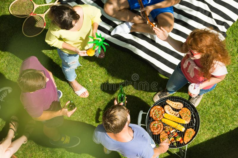 Summer day in the garden. Happy young people spending summer day grilling in the garden royalty free stock image