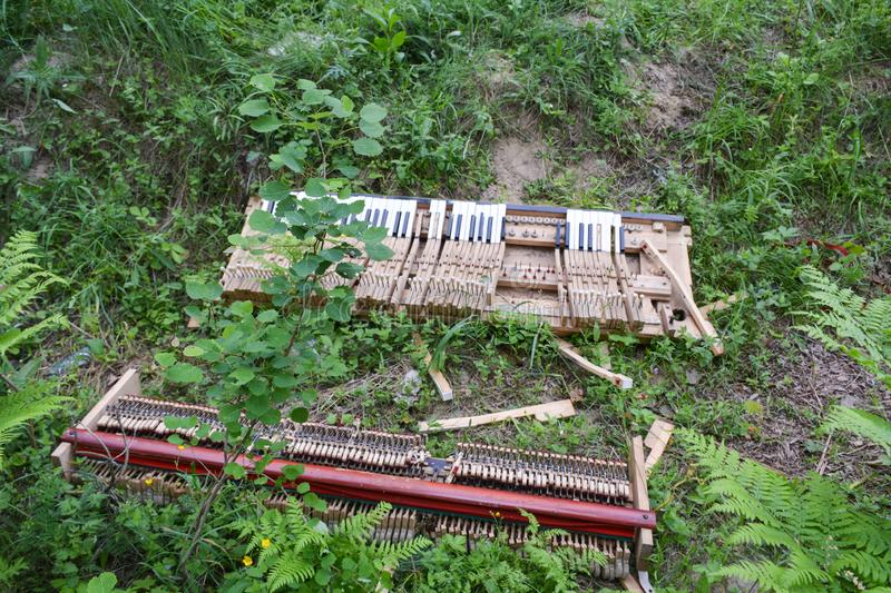 Broken piano lying in green grass. Summer day gives the photographer an amazing discoveries royalty free stock photos