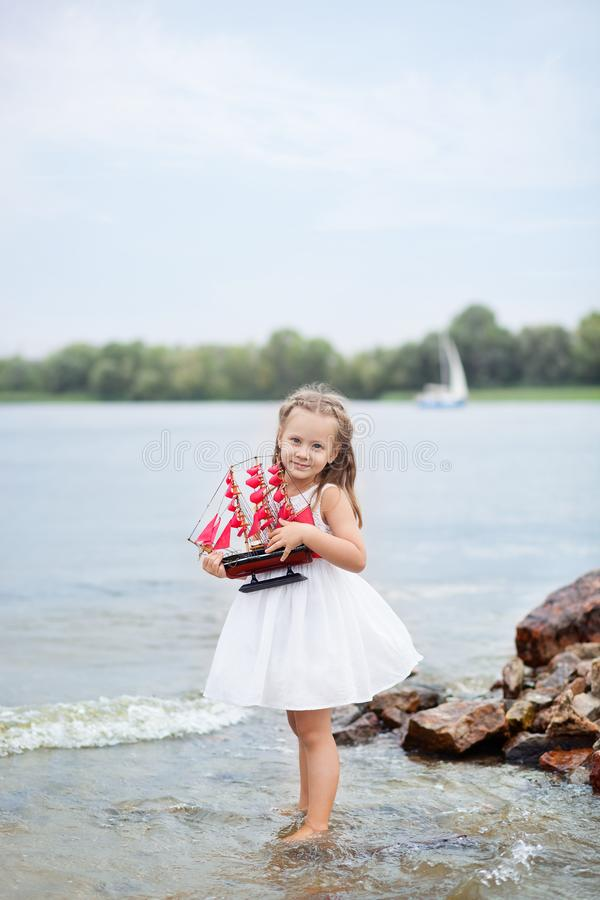 Summer day. Happy childhood carefree game on the open sand. The concept of rest. Little cute girl and scarlet sails. Girl sitting royalty free stock photos