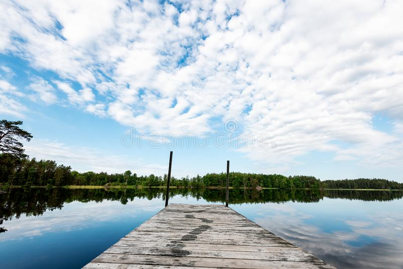Summer day by lake. Wooden peir in forest lake a beautiful summer day in Sweden, with blue sky with white clouds royalty free stock photography
