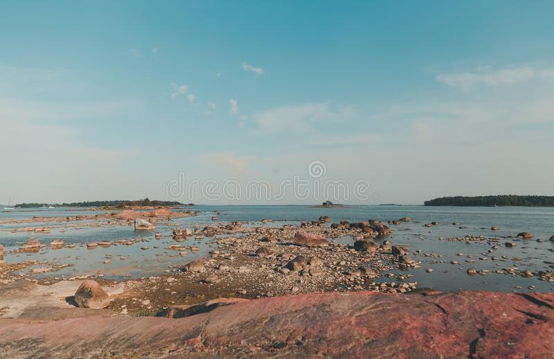 Finland Helsinki, shallow waters at Lauttasaari with the stones visible on a summer day. Summer day at Lauttasaari, Helsinki Finland, with a stone shore royalty free stock images