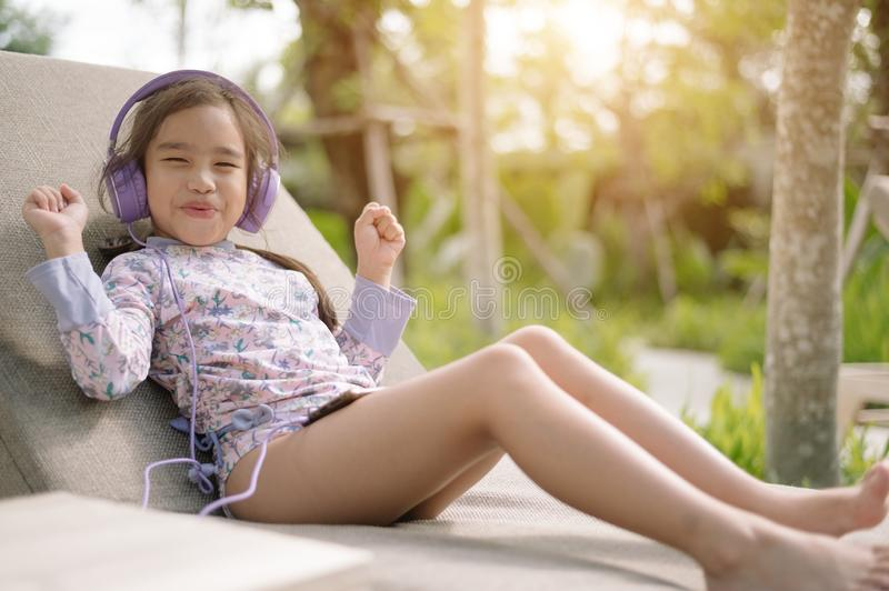 Summer day lifestyle  Young asian girl relax  listening to music in  swimming pool at the beach resort outdoors the hotel. Concept stock images