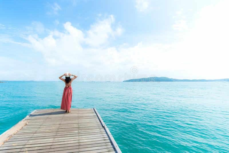 Summer Day. Smiling women relax and wearing red dress fashion standing on the wooden bridge over the sea, blue sky background royalty free stock photos