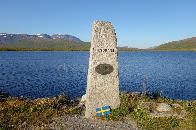 Stone marking the border crossing between Sweden and Norway at E12 road to Mo I Rana. Umbukta lake in the back. Summer day. Stone marking the border crossing royalty free stock photos