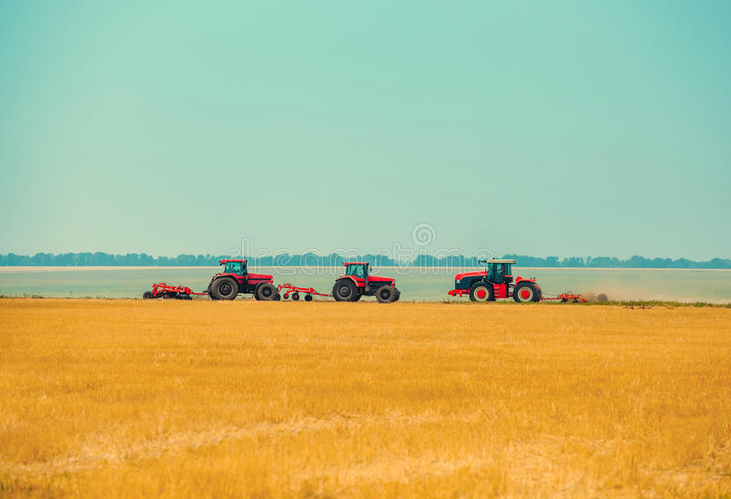 Summer day three tractors to plow, plow the soil on sloping, cornfield. Agricultural land treatment before planting royalty free stock photography
