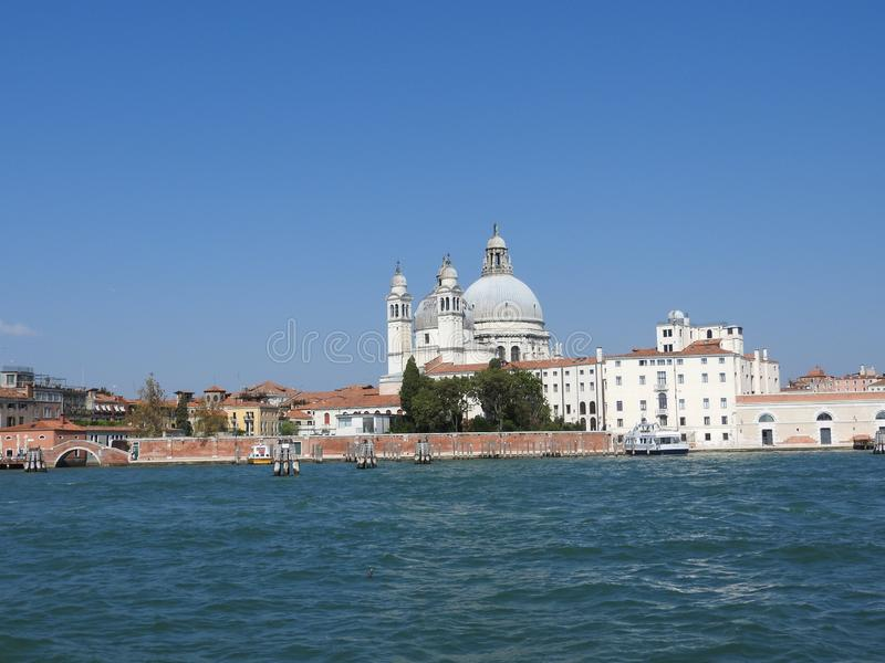 Summer day view from the water to the Venetian lagoon with the Basilica of Santa Maria della Salute in Venice, Italy royalty free stock image