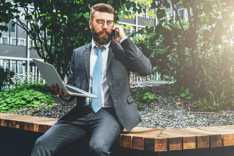 Summer day. Young bearded businessman in suit and tie sitting in park on bench, holding laptop and talking on cell phone royalty free stock photography