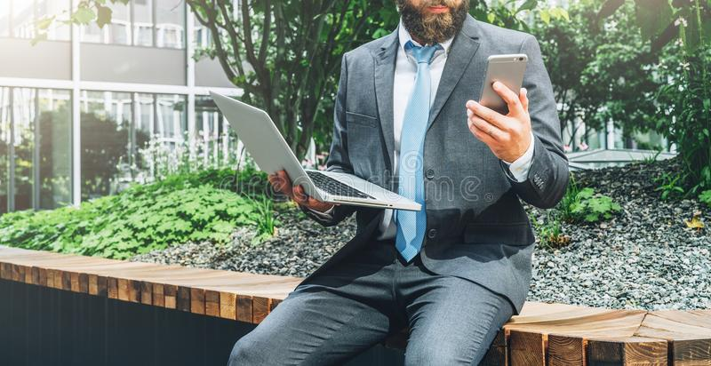 Summer day. Young bearded businessman in suit and tie sitting in park on bench, holding laptop and using smartphone royalty free stock image