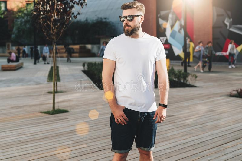 Summer day. Young bearded hipster man dressed in white t-shirt and sunglasses is stands on city street. Mock up royalty free stock photography