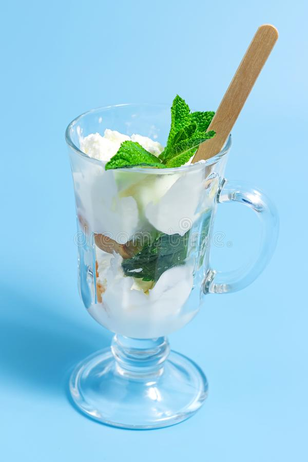 Summer dessert. ce cream with fruit and mint leaves in glass on a blue background stock photography