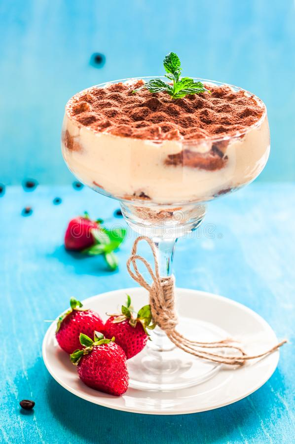 Summer dessert tiramisu, classic cheesecake with strawberries decorated with mint leaves. On a light blue wooden table, bright sun stock photo