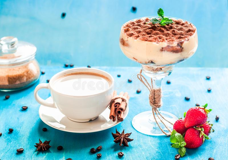Summer dessert tiramisu, classic cheesecake with strawberries decorated with mint leaves. On a light blue wooden table, bright sun. Summer dessert, classic royalty free stock photo