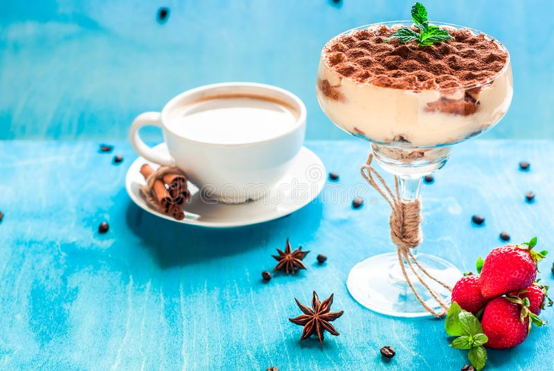 Summer dessert tiramisu, classic cheesecake with strawberries decorated with mint leaves. On a light blue wooden table, bright sun. Summer dessert, classic royalty free stock photography