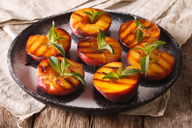 Summer dessert: grilled Peaches with powdered sugar and fresh mi stock image