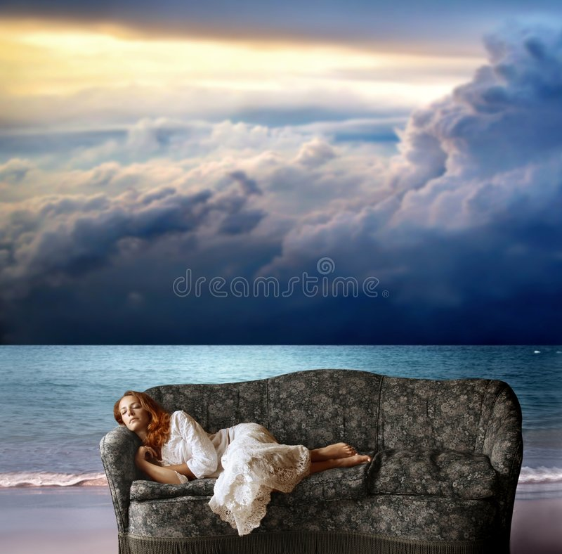 Summer dream. A woman sleeping on the sofa on the beach