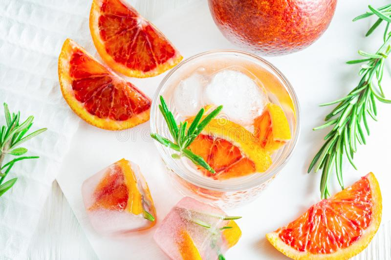Summer drink with blood orange and rosemary on white wooden background. Flat-lay, top view stock images