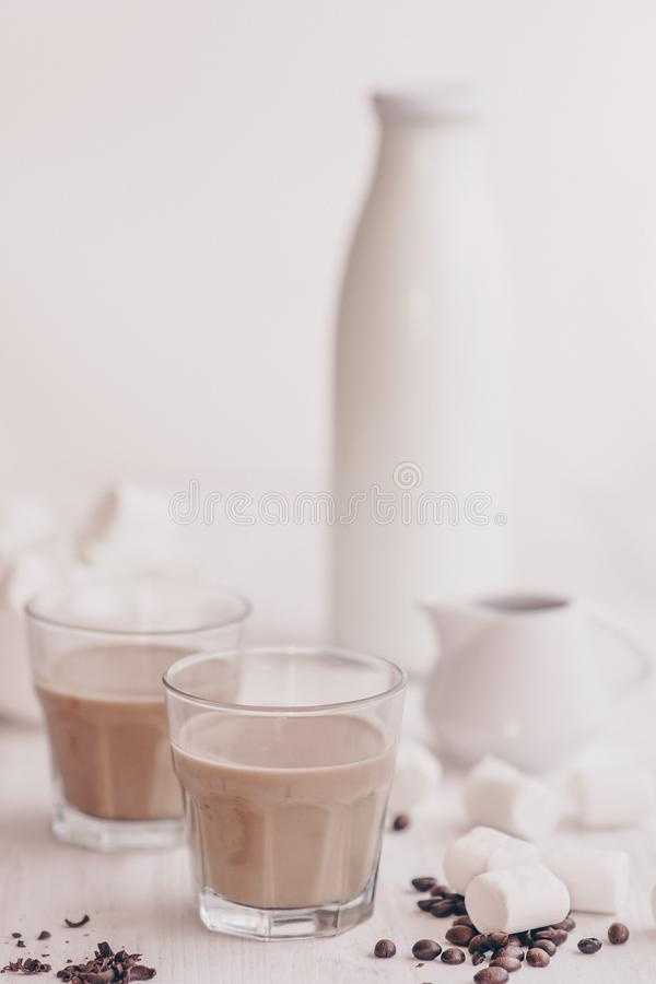 Summer drink. Cold coffee with milk and chocolate. Light background. Iced coffee. Concept of a cooling drink. Marshmelow and coffee beans on the table royalty free stock photos